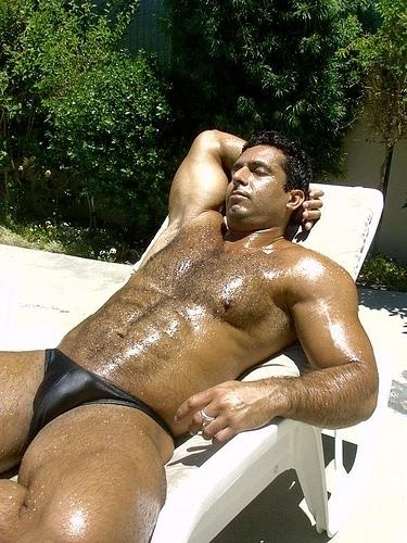 Um peludão de sunga deitado ao sol